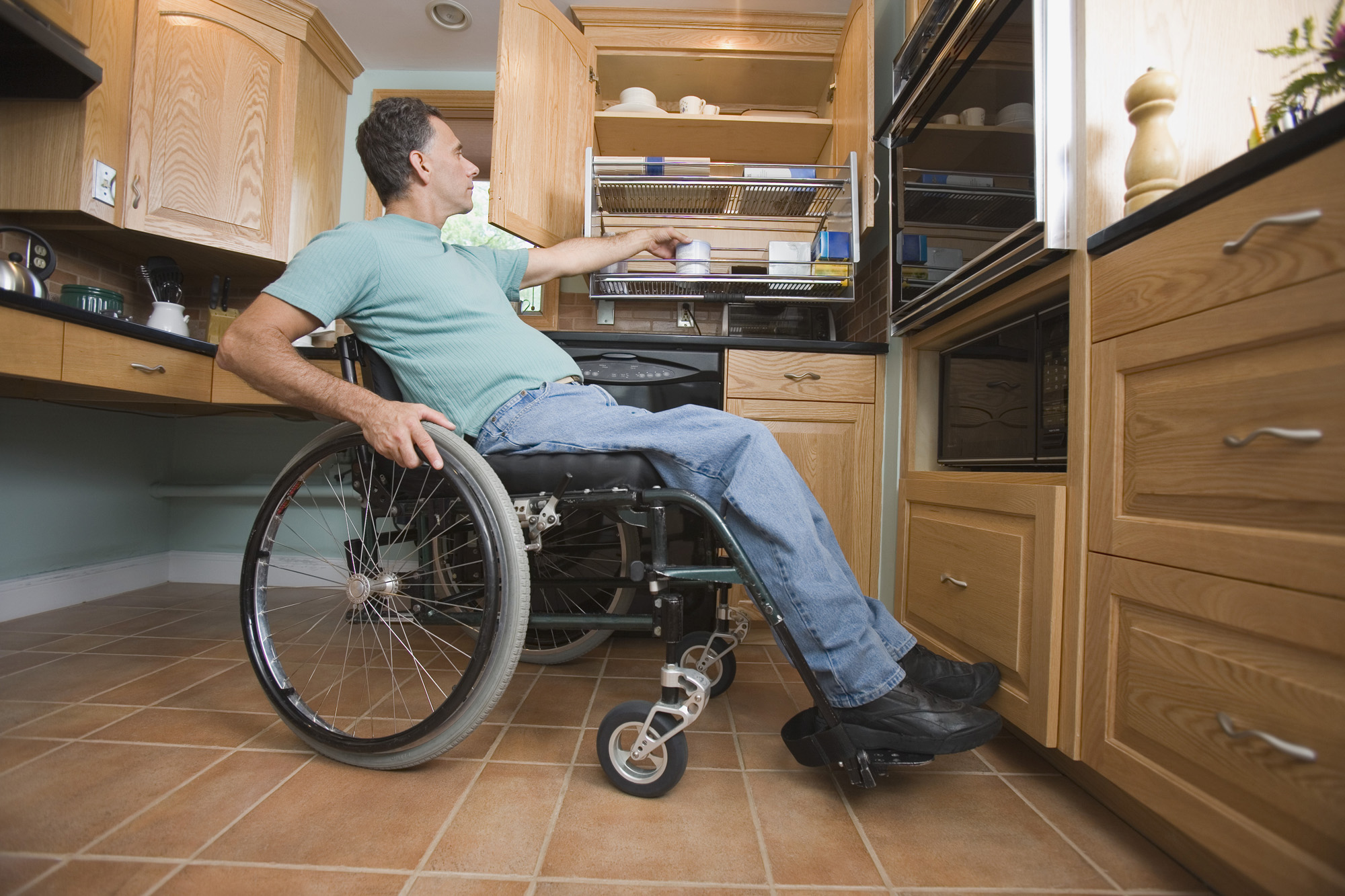 Man in wheelchair working in his kitchen
